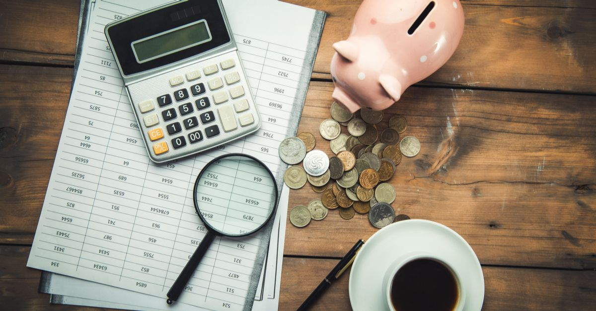 A desk with paperwork, a calculator, a magnifying glass, a bunch of coins, a cup of coffee, and a piggy bank on it