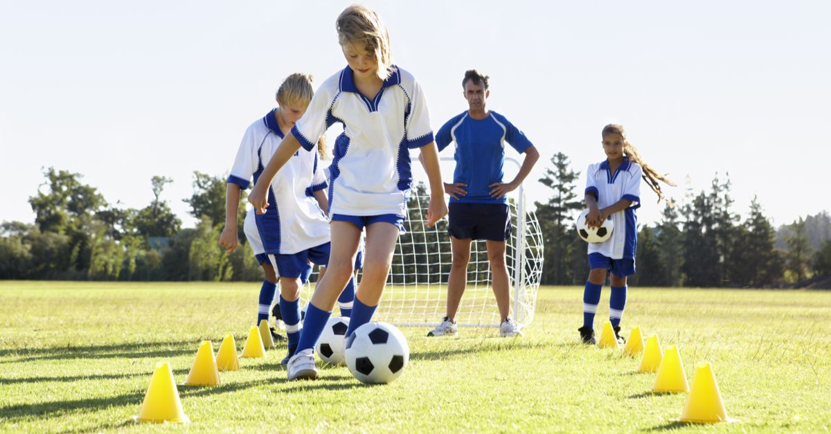 A photo of four children at football trials, dribbling the ball through small yellow cones while the coach watches